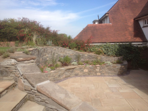 Raised stone wall with steps and flower beds