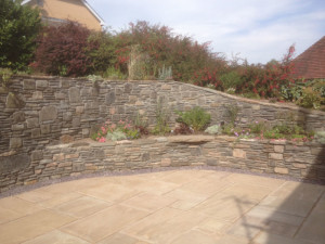 Raised stone wall with tiered flower beds